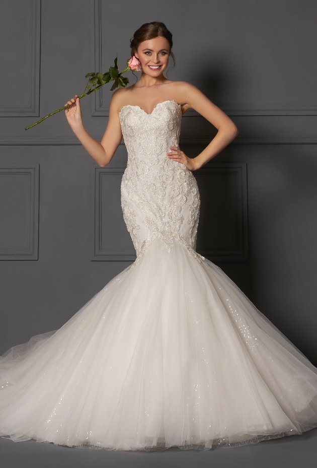 Bride wearing a Danielle Couture lace fishtail gown holding a rose