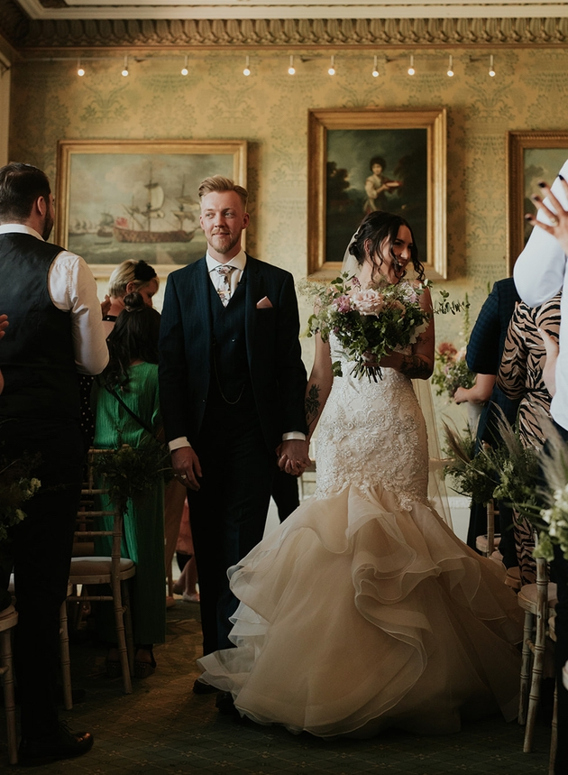 Happy newlywed couple walking down the aisle styled by London's ByChenai Events