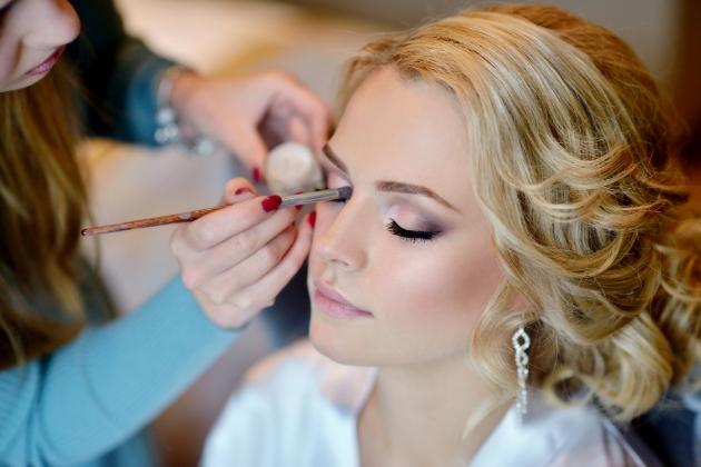 A beautiful bride having her makeup applied by a makeup artist