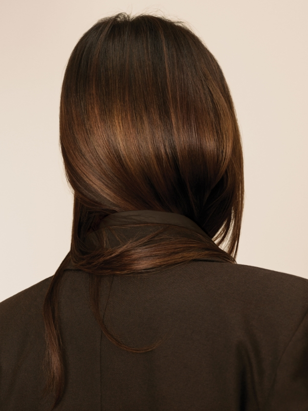 Back of woman's head. Her hair is wrapped around her neck and its super-shiny