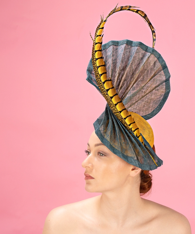 Woman wearing large grey fascinator with feather by London's Katherine Elizabeth Millinery