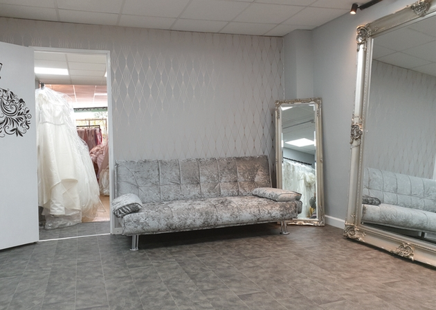 Interior of Best Dress 2 Impress bridal boutique in London with grey sofa and ornate mirror
