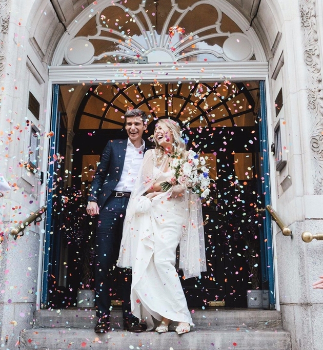 Newlywed couple with confetti on steps of Chelsea Old Town Hall