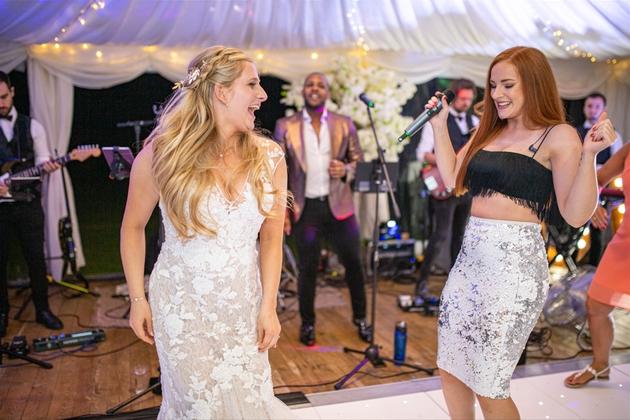 Bride dancing with singer at wedding reception.