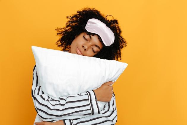 Woman ready for her beauty sleep with pyjamas, sleep mask and pillow