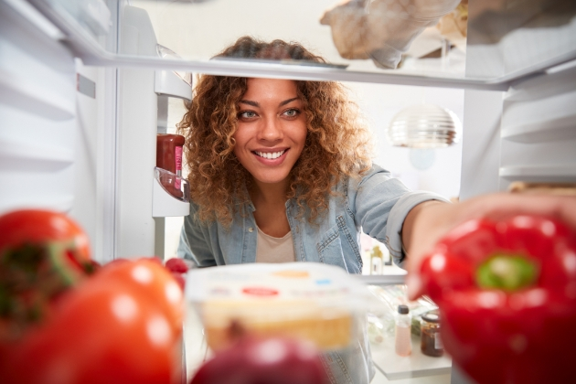 Woman reaching into the fridge for a red pepper