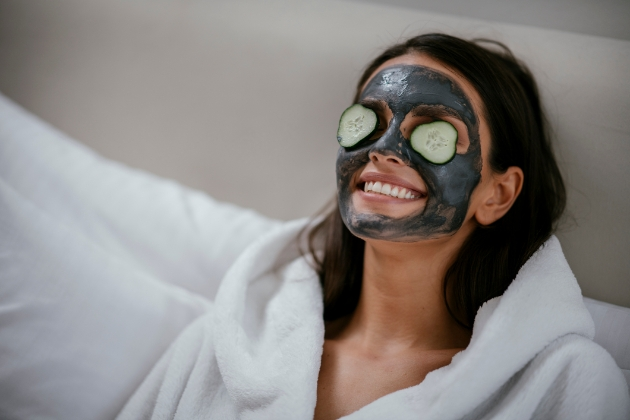 Woman wearing a face mask with cucumber slices over her eyes.