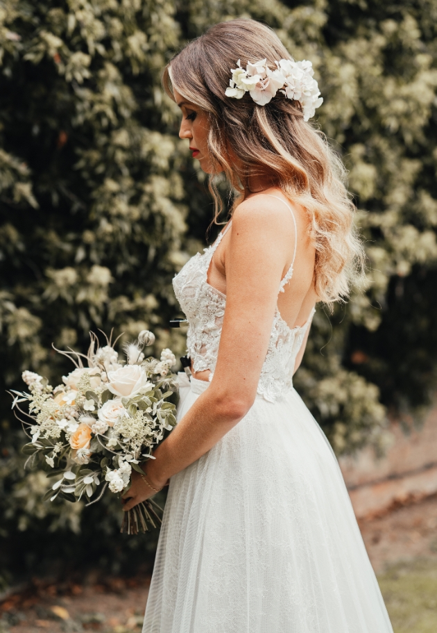 Bride in meadow with long wavy hair and bouquet