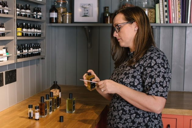 woman standing a work benches with perfume bottle and ingredients