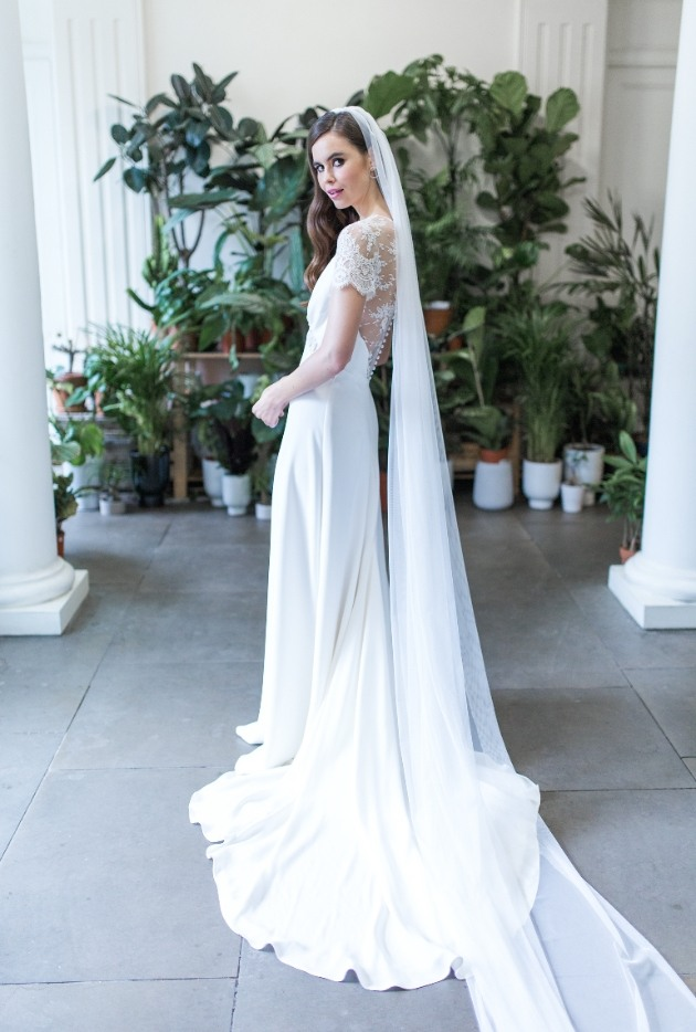 Bride in ivory wedding dress with lace top and veil.