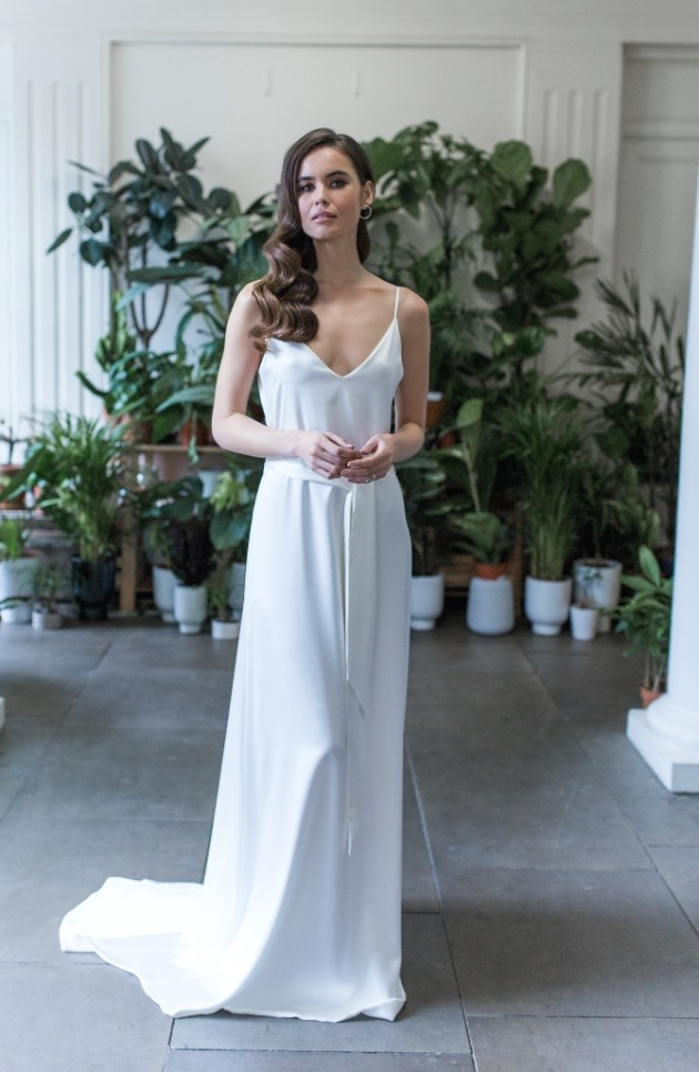 Bride wearing simple ivory wedding dress with spaghetti straps.