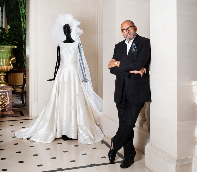 Bruce Oldfield OBE poses at The Lanesborough in London with bridal dress on mannequin