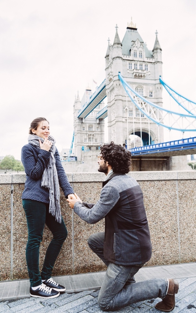 Man proposing to woman by Tower Bridge in London.