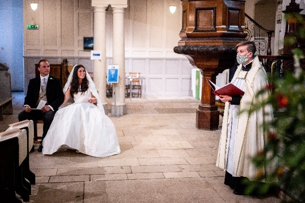 Couple getting married in church with vicar in face mask.