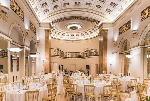 Bride walking through the ballroom at the historic Lansdowne Club venue in Mayfair