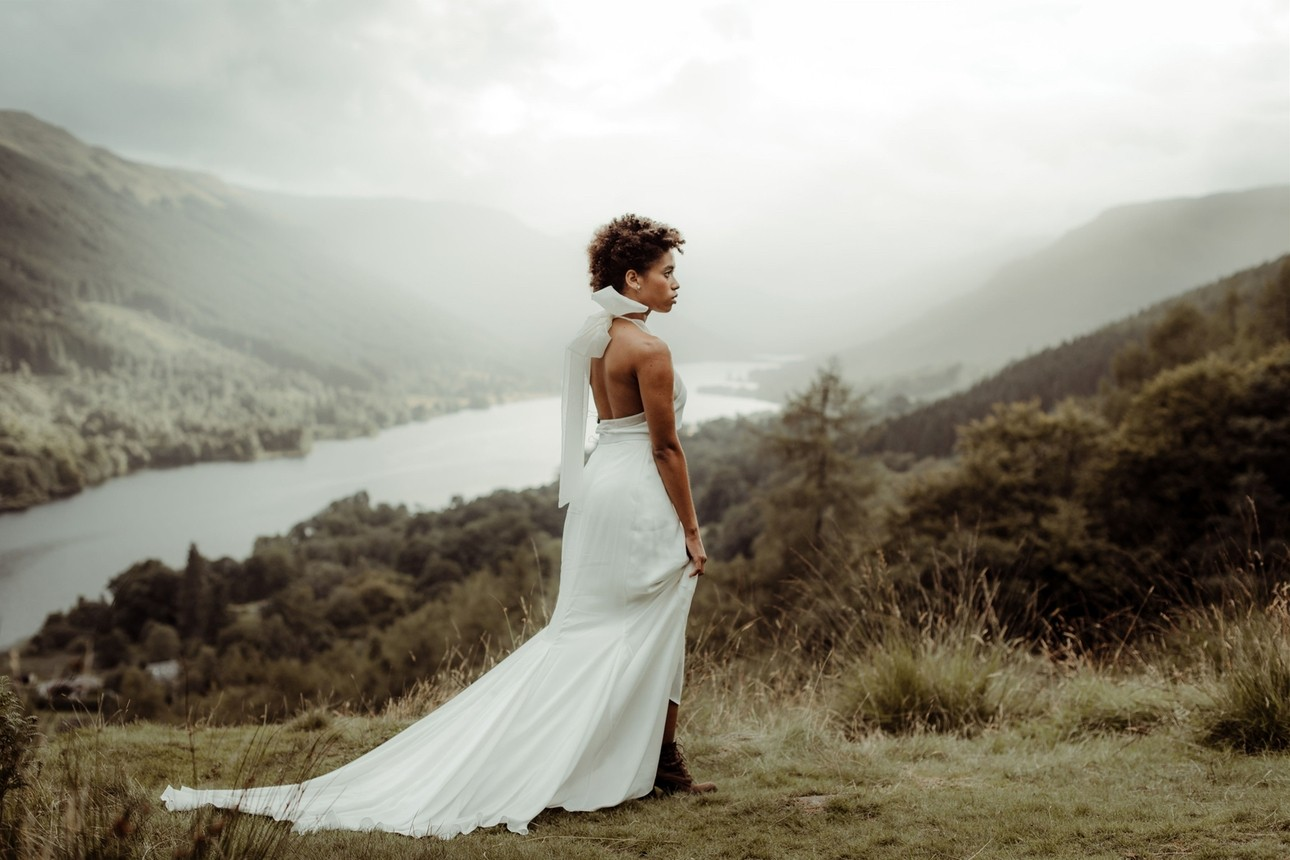 Bride stood by lake wearing bridal gown with bow detail by London bridal designer Paper to Lace