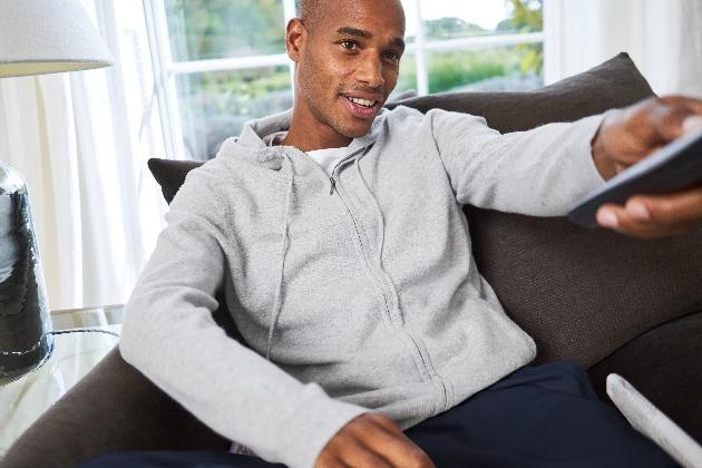 man in loungewear on sofa holding remote control