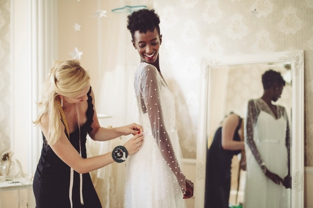 Bride having dress altered by seamstress.