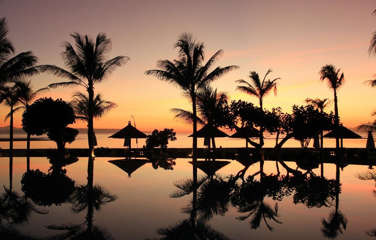 Beach at parasols at sunset in Bali.