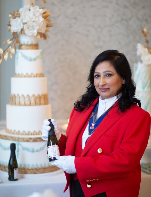 London Toastmaster Sonal Dave with bottle of champagne and ivory wedding cake.
