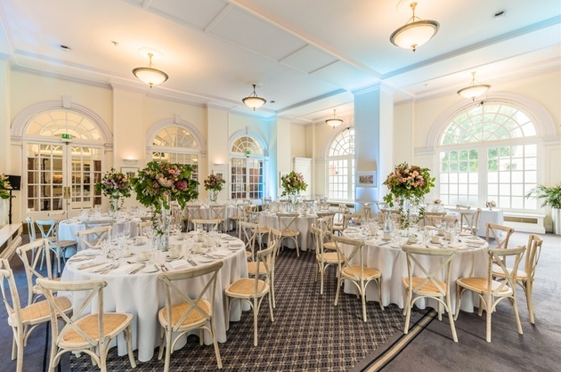 Interior of BMA House wedding venue in London dressed for a wedding with flowers and round tables