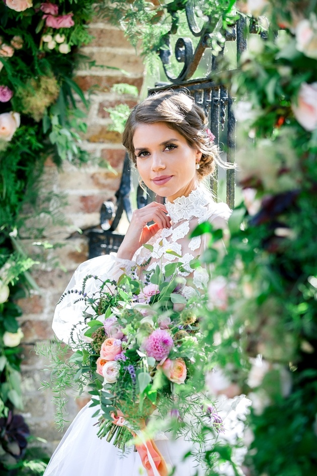 Bride wearing lace dress holding bouquet and surrounded by flowers, styled by Hair and Makeup by Gabrielle