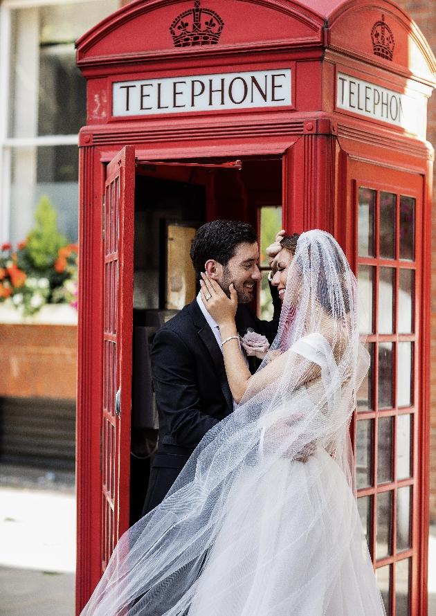 Couple pose outside phonebox