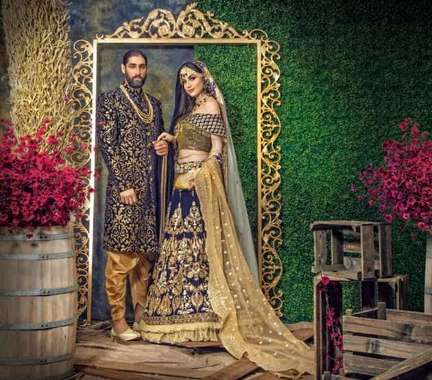 Bride and groom in navy and gold outfits designed by Oorvi Desai.