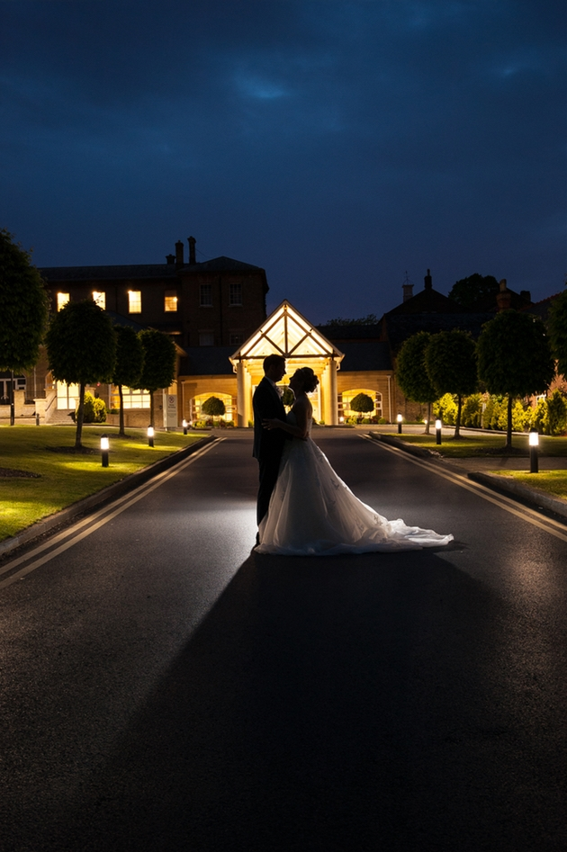 Newlywed couple at night in front of wedding venue.