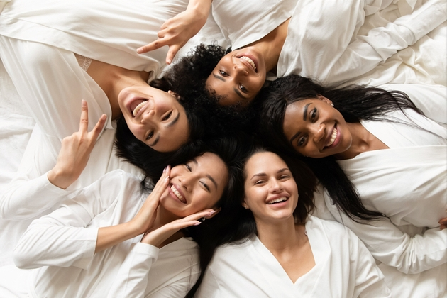 Smiling brides on bed.
