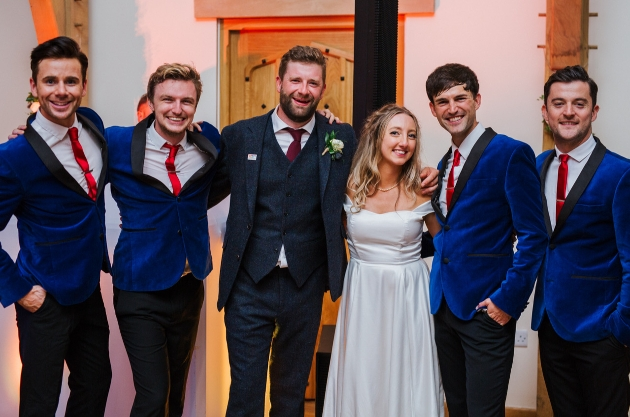 four band members with bride and groom