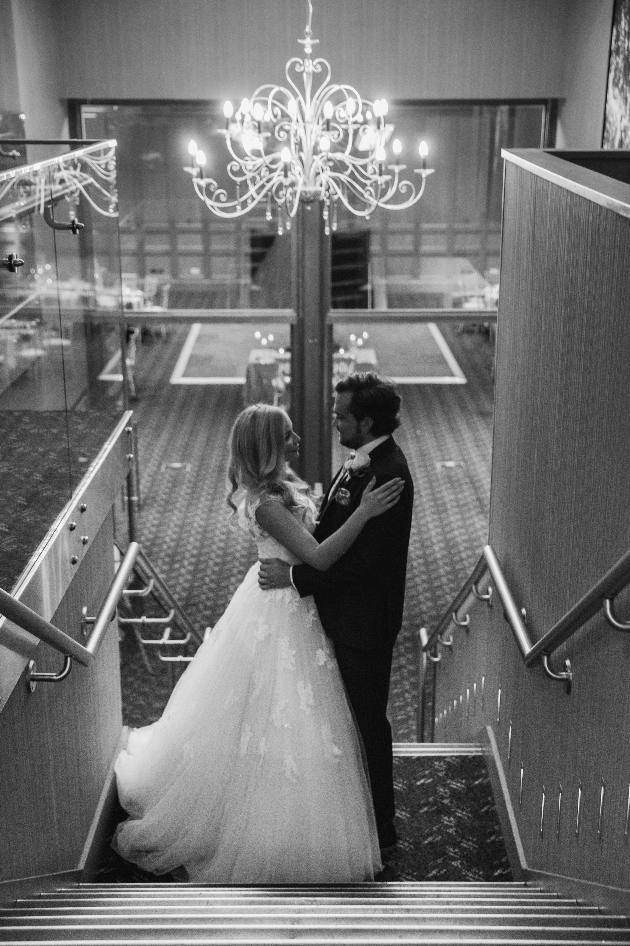 couple standing on stairs below chandelier