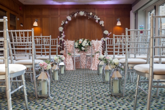 chair set up for ceremony in a wood panelled room with lanterns in aisle