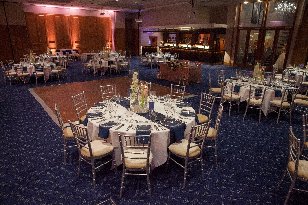 wedding breakfast tables set in in large room with blue carpet