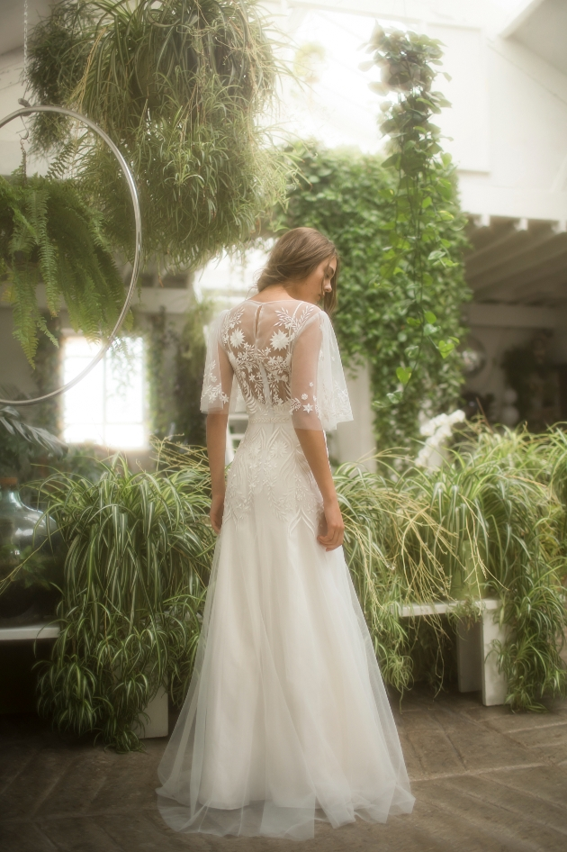 model in a wedding dress with a lace cape