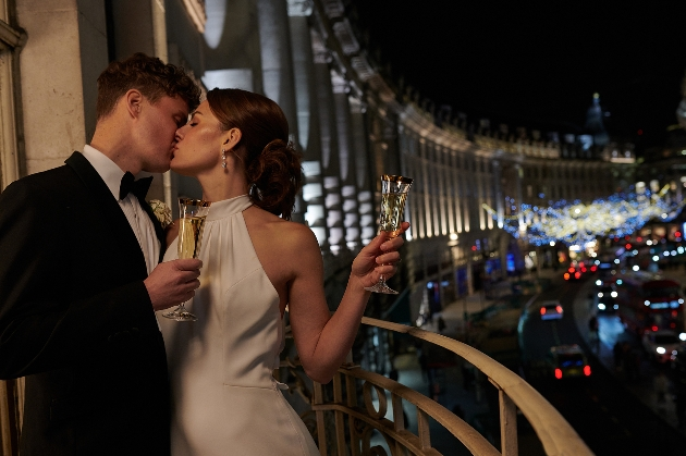 models in bride and groom outfit on a venue balcony with london skyline in background
